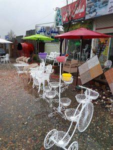 محوطه بیرونی فروشگاه مبلمان باغی در یک روز بارانی زیبا با نمایی از دوچرخه فلزی فلاور باکس ست مبلمان آلومینیوم