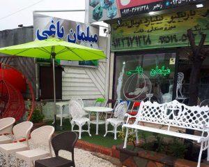 محوطه بیرونی فروشگاه مبلمان باغی همراه با نیمکت آلومینیومی سفید ست چهارنفره طاووسی و صندلی های پلیمری و چتر و تاب