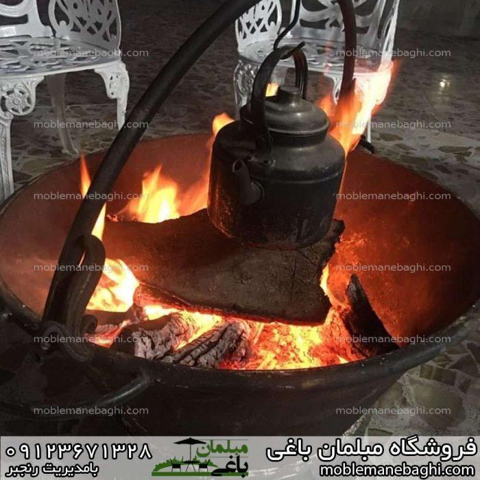 کتری بر روی آتش در آتشدان ذغالی در یک دورهمی زیبا در فضای باز آلاچیق با طراحی میزوصندلی مرغابی
