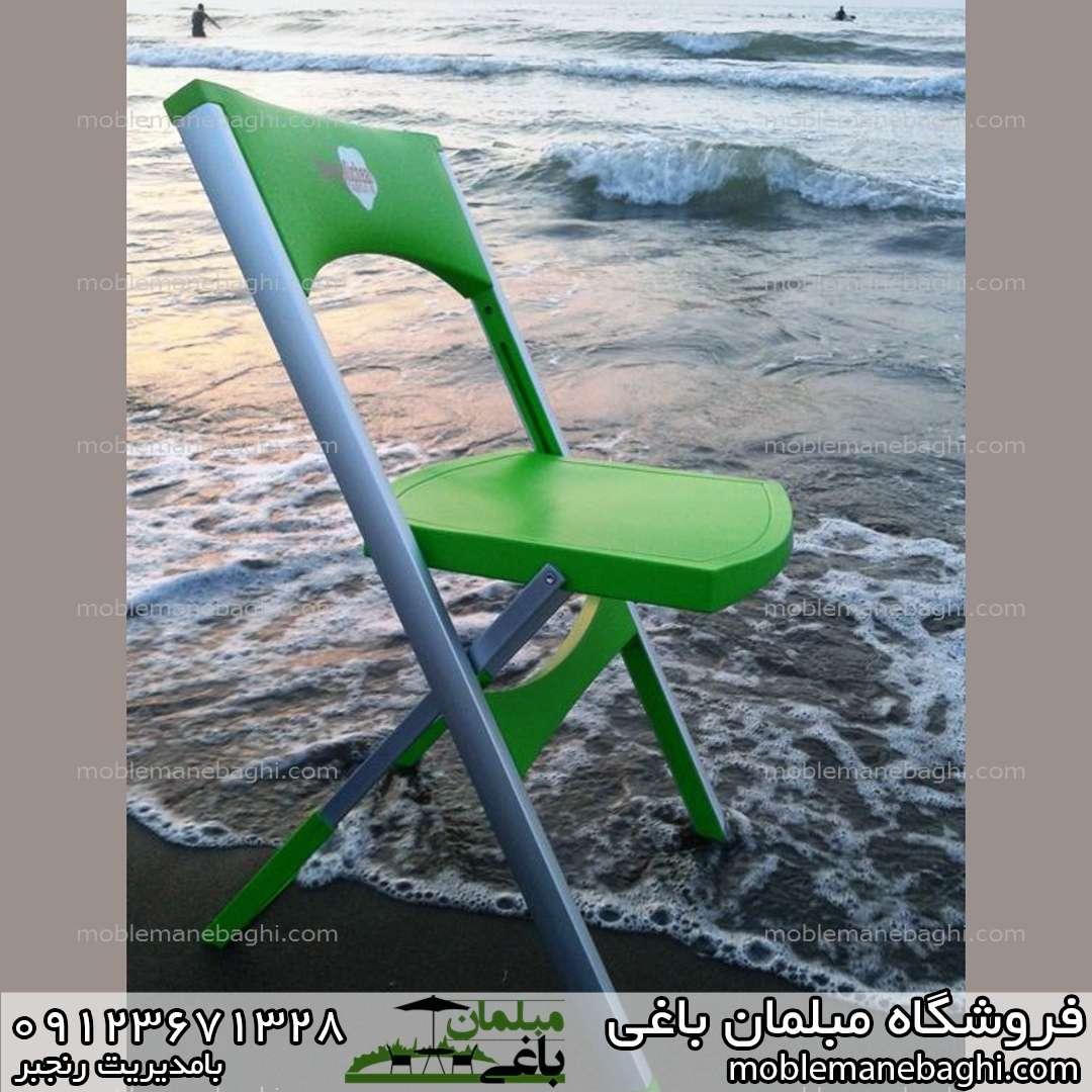 صندلی تاشو مسافرتی در کنار ساحل زیبای شمال زیر آن موج های کفی دریا