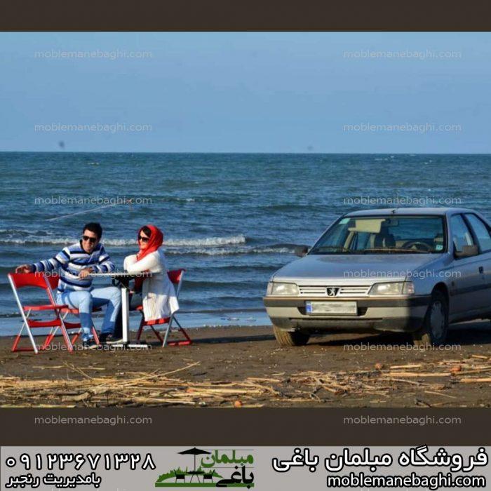 صندلی مسافرتی دونفره تاشو به همراه میز مورد استفاده زن و شوهری جوان در سفر شمال در کنار دریا بسیار خاص و لاکچری