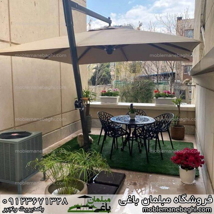 صندلی پلی کربناتی مدل درختی ست پنج و شش نفره بر روی چمن مصنوعی به همراه چتر پایه بغل در تراس آپارتمانی شیک و زیبا