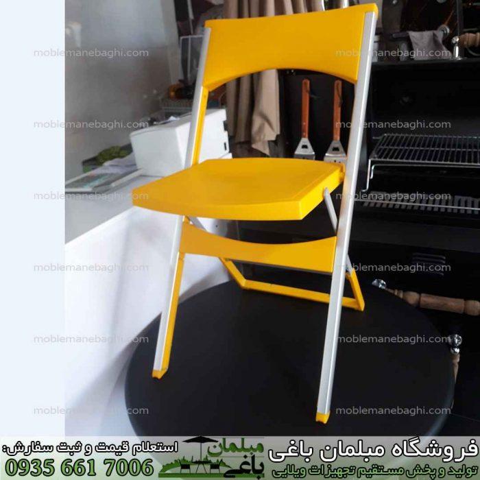 صندلی تاشو مسافرتی مدل کلاسیک به رنگ زرد بر روی میز تاشو مسافرتی به رنگ مشکی در مرکز پخش صندلی تاشو مخصوص فضای باز و صندلی استخری و مسافرتی باکیفیت و قیمت مناسب