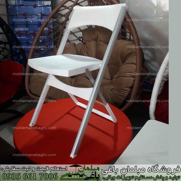 صندلی تاشو مدل کلاسیک با پایه های نشکن و مقاوم آلومینومی بسیار کم جا مخصوص مسافرت و فضای باز باغ و ویلا به رنگ سفید بر روی میزتاشو مسافرتی به رنگ قرمز بسیار باکیفیت