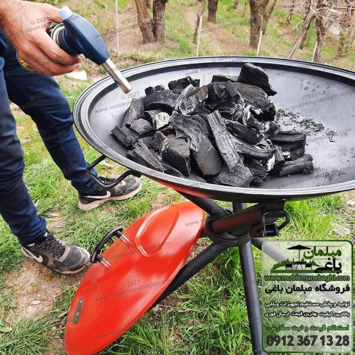 منقل کبابپز مسافرتی پارمیس پر شده از ذغال و درحال روشن کردن ذغال با استفاده از فندک مخصوص
