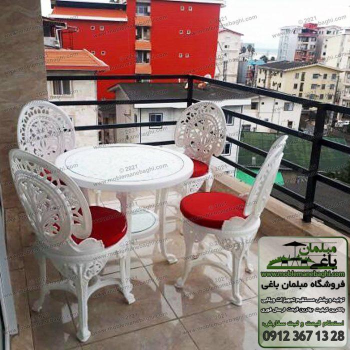 ست مبلمان پلیمری مدل طاووسی شامل چهار صندلی پلیمری یا پلاستیکی درجه یک همراه با میز پلاستیکی چهارنفره گرد به همراه تشک قرمز در تراس یک آپارتمان در شهرک ویلایی