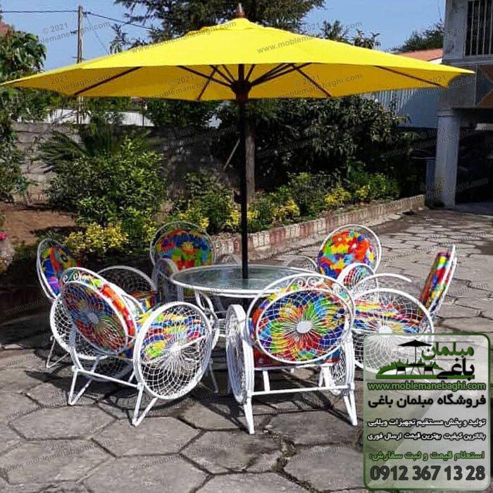 ست مبلمان باغی مخصوص فضای باز مدل صندلی فلزی گلبرگ یا کالسکهای رنگ آبی استخری به همراه سایهبان باغی مدل چترباغی پایه وسط رنگ زرد در محوطه یک ویلای زیبا