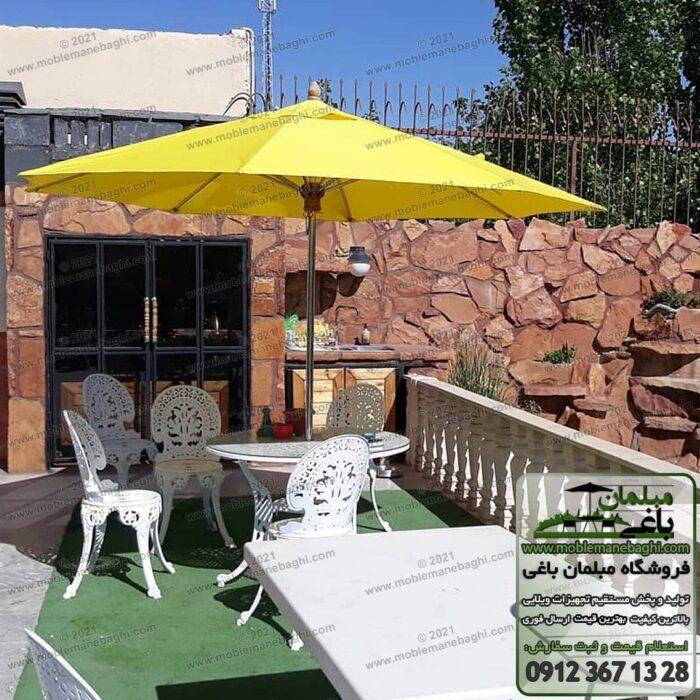 سایهبان باغی مدل چتر باغی پایه وسط رنگ زرد بر روی مبلمان فضای باز آلومینیومی مدل طاووسی در تراس یک ویلایی لاکچری و زیبا