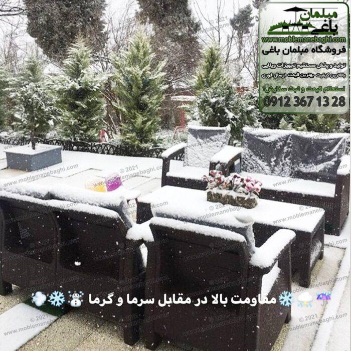 ست شش نفره مبل حصیری پلیمری مخصوص فضای باز و مقاوم در شرایط آبوهوایی مختلف با بارش برف بر روی آنها در حیاط و فضای باز یک ویلای زیبا و سفید پوش از بارش برف