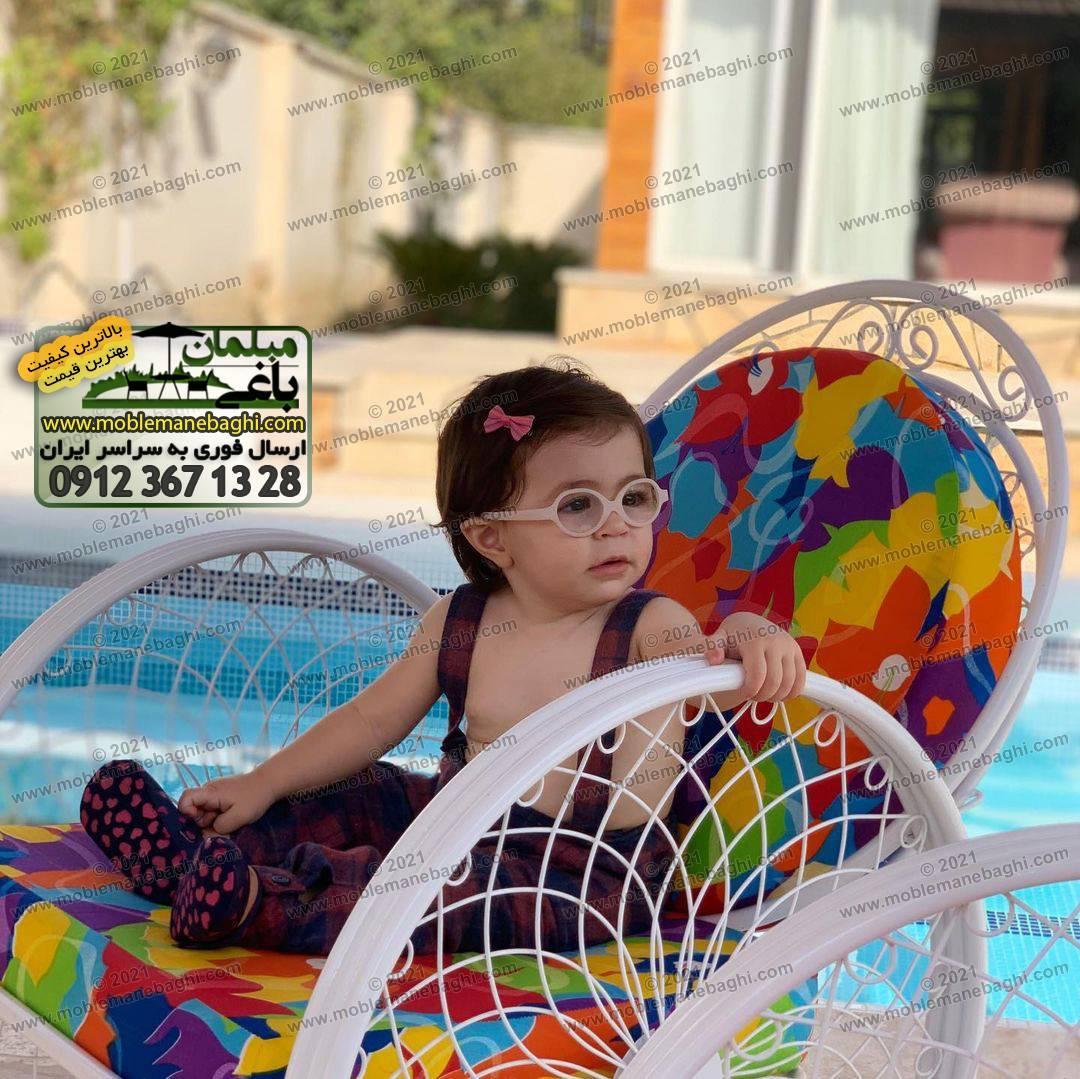 صندلی فلزی گلبرگ با تشک رنگی شاد و یک کودک زیبا با نام تامای نشسته بر روی آن در کنار استخر ارسالی مشتری از چهارباغ کرج
