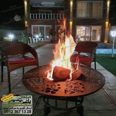 میز آتشدان گرد که یک محفظه آتش درون آن قرار دارد و کاربری آن ذغالی یا همان هیزمی است بسیار شیک و زیبا به همراه دو عدد صندلی حصیری مخصوص فضای باز در محوطه یک ویلای زیبا