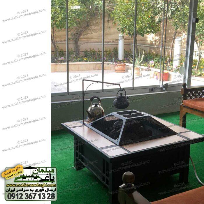 میز آتشدان چهارگوش گازی ذغالی (هیزمی) به همراه کتری و قوری بر روی نگهدارنده کتری در ویلایی شیک با پنجره های بلند با ویویی عالی از تراس